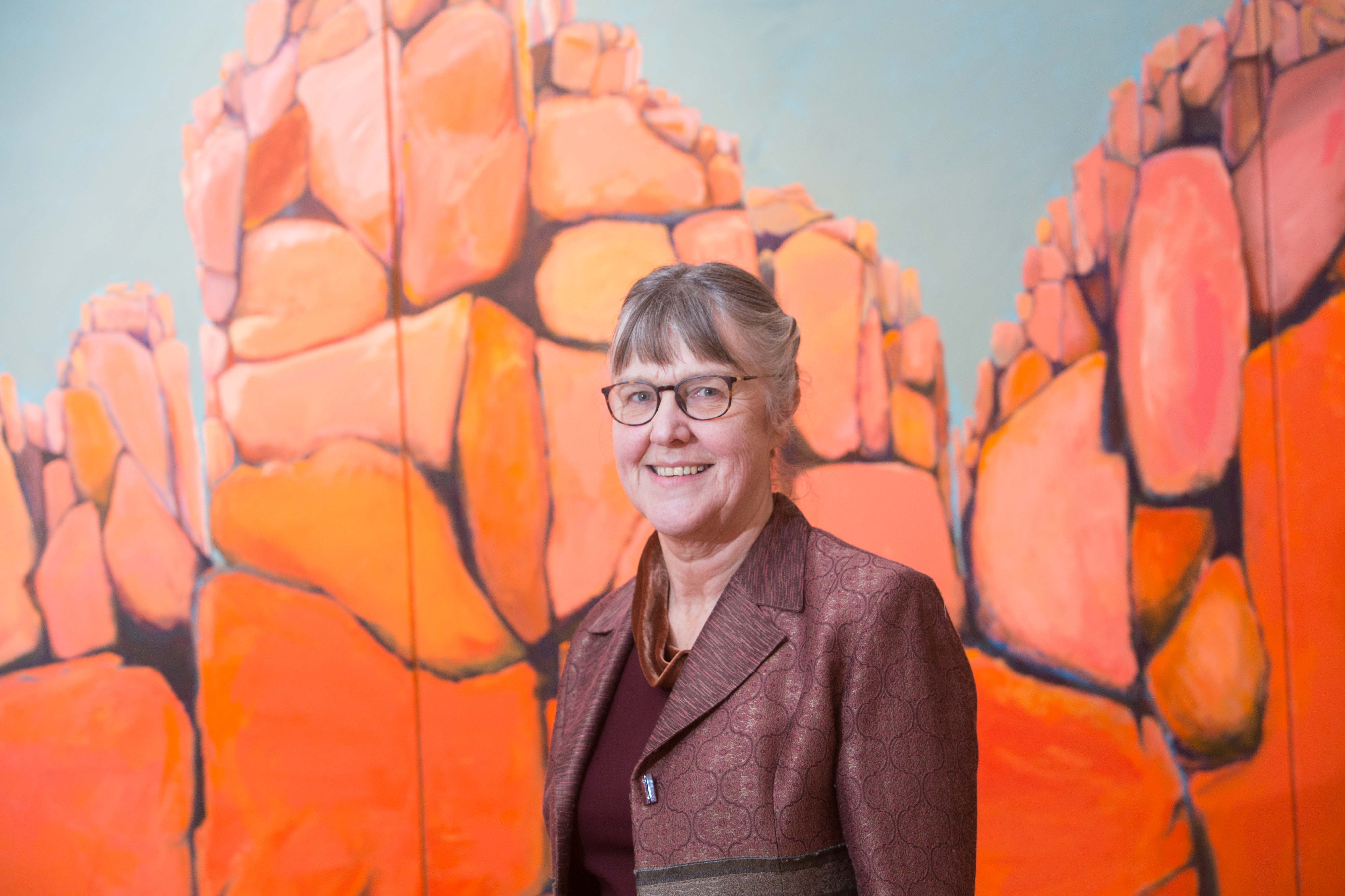 "Artist Anna Moore in front of her painting ""Safe Place For Rhino - Waterburg Plateau"""